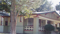 A house with a front porch and red and white painted trim.