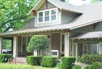 A large house with shrubs in front.