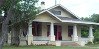A small yellow house with a large front porch.