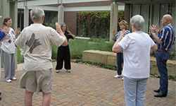 Adults participating in Tai Chi in an outdoor setting
